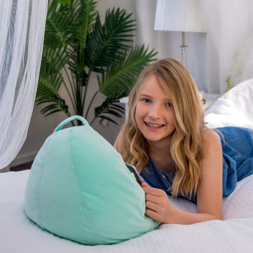 A teen reads from her iPad or tablet hands free with it resting on a mint green velvet iCrib bean bag. The carry handle is visible.
