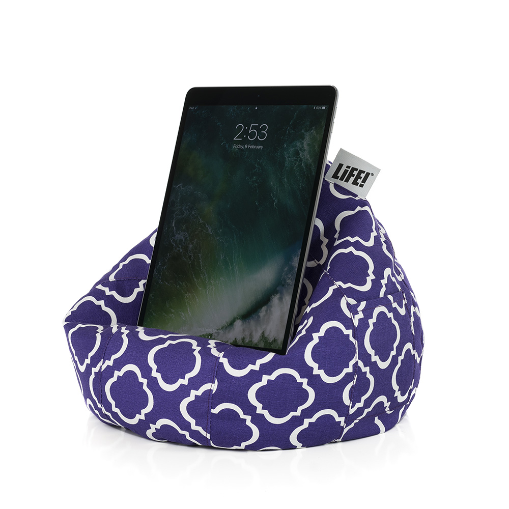 An iPad sits in an iCrib tablet holder rest stand. Its purple with a white geometric print.