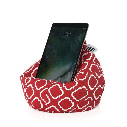A tablet rests on the iCrib iPad bean bag tablet holder cushion. It is red with a white geometric print