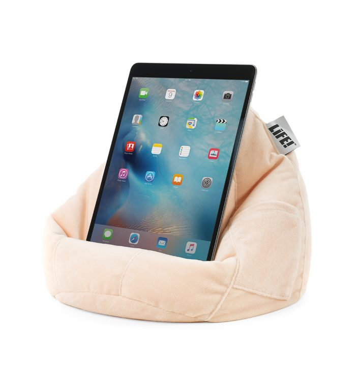 An iPad rests on a peach pink velvet tablet holder book rest iPad stand