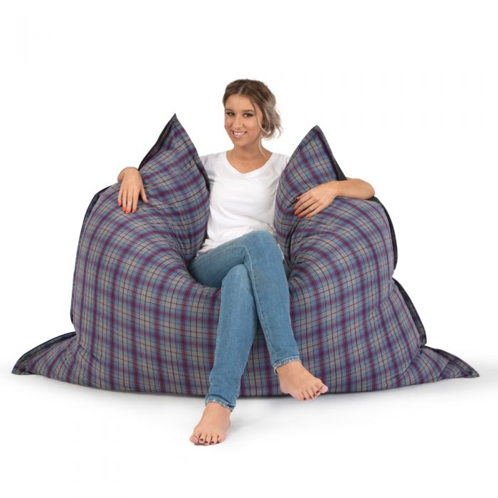Woman sitting in the arcadia dreams supersize bean bag, purple and grey check