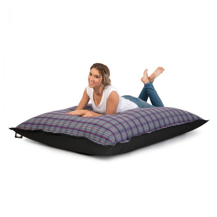 Women lays on a supersize arcadia dream bean bag. It is a large pillow shape and she fits on it easily. The top is a purple and grey check flannelette and the bottom a heavy duty black material.