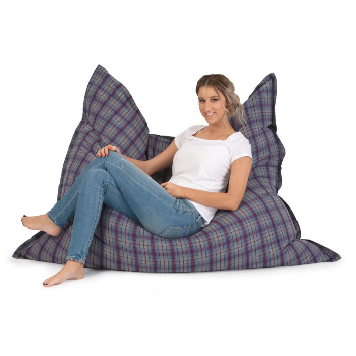 Women reclines in a purple and grey check arcadia dreams super size bean bag with purple and grey check