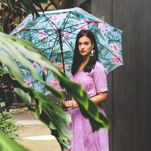 A girl in a pink dress with toucan earrings holds a large, tropical print belvedere rain umbrella. The print is blue, green and pink.