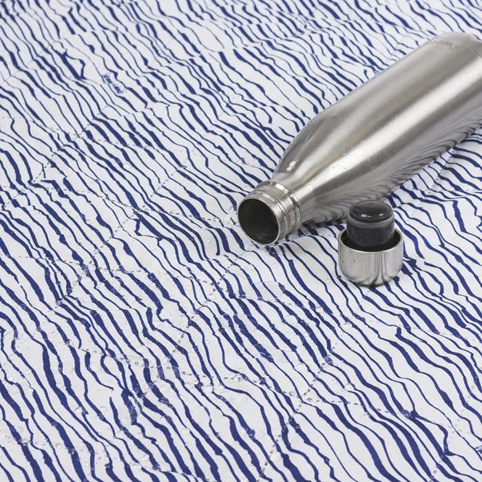 Close up of the quilting pattern and water resistant properties of the blue and white marine print adventure mat