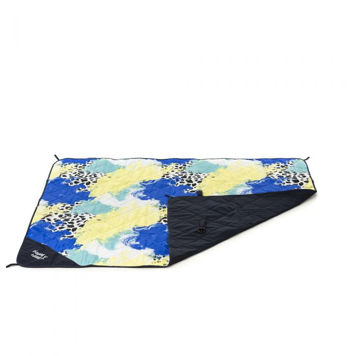 Tier print adventure mat, beach blanket, picnic rug with the corner rolled over to show the contrast underside and closing clasp