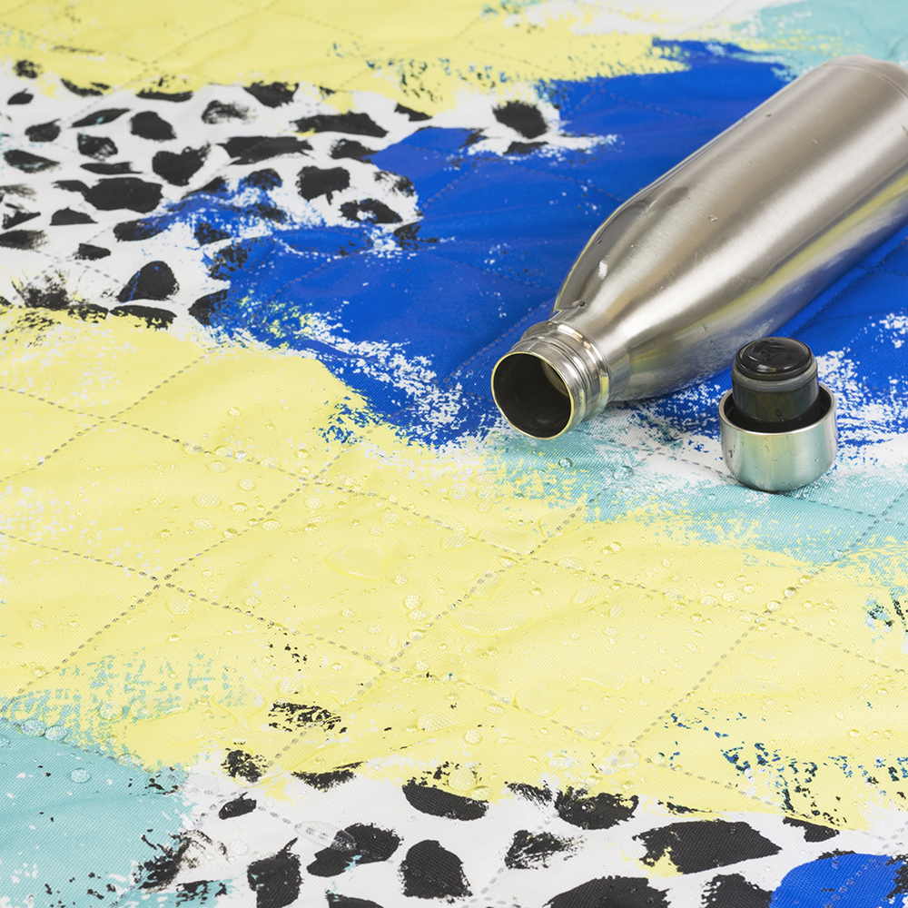 Close up of the tier yellow, green, blue and white print showing the quilting and spill resistant surface