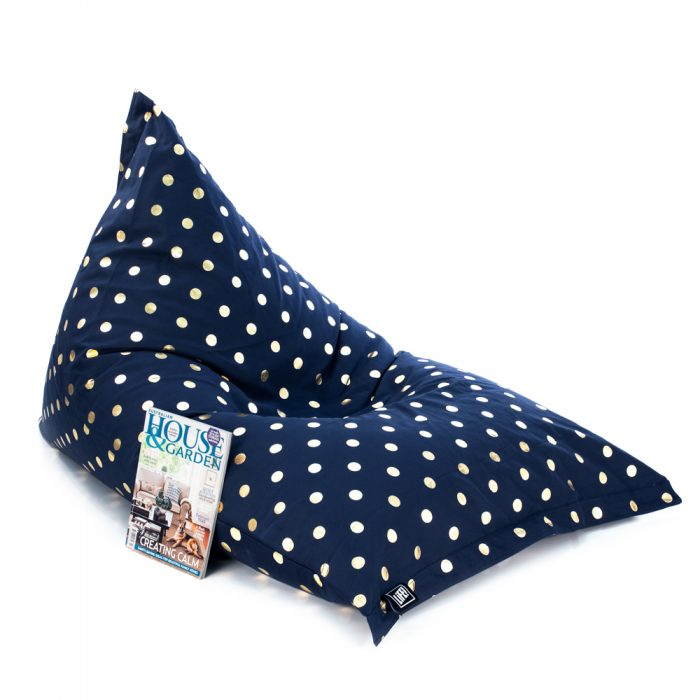 Oblique view of the sunnyboy shaped bean bag in navy gold coin print with a magazine resting against it