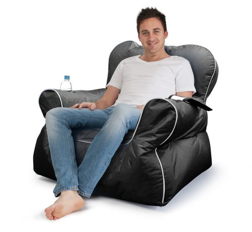 Man sitting in large black arm chair shaped bean bag with drinks holder