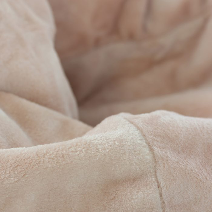 Close up of the fabric detail on the super size peach pink faux fur tear drop shaped bean bag