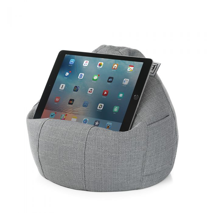 A tablet sits on a grey linen look iCrib iPad rest holder stand cushion bean bag. A storage pocket is visible.