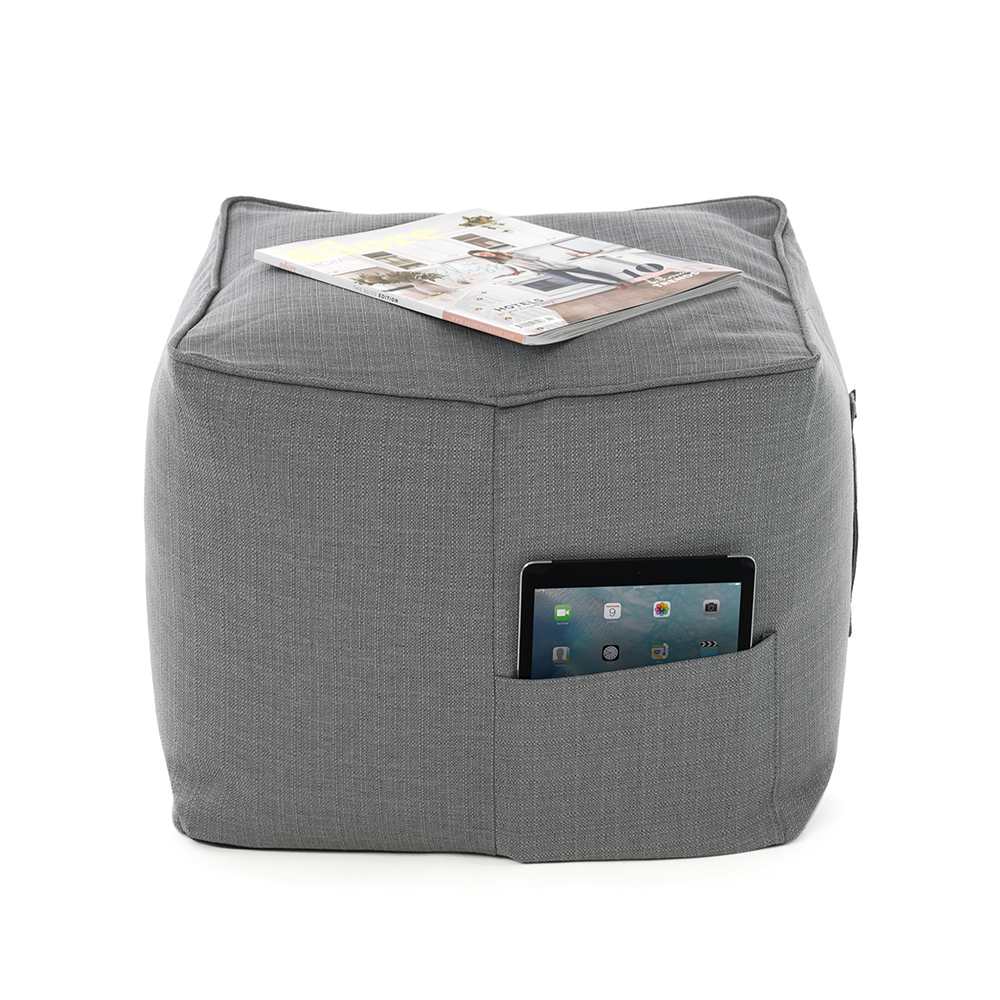 Grey linen look ottoman with a magazine on top of it and an iPad or tablet in the storage pocket