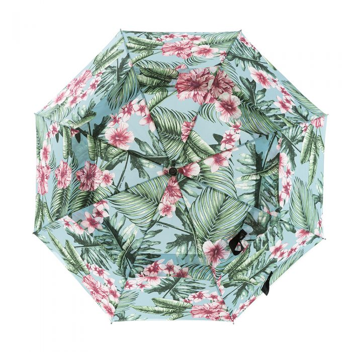 The belvedere print rain golf umbrella shown open from above. The large scale tropical print features pink hibiscus and frangipani on a blue background with green leaves.
