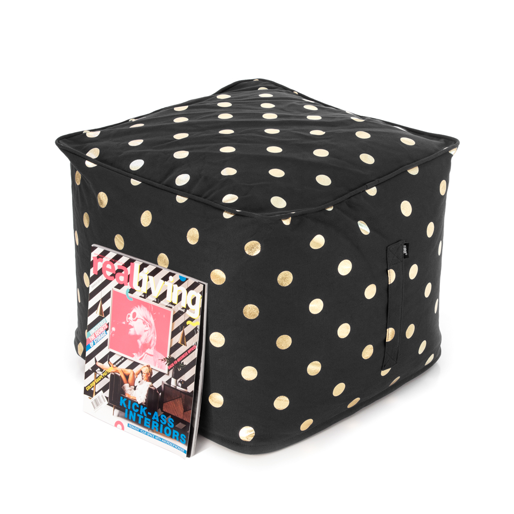 A magazine rests upon a black ottoman with a metallic gold coin print