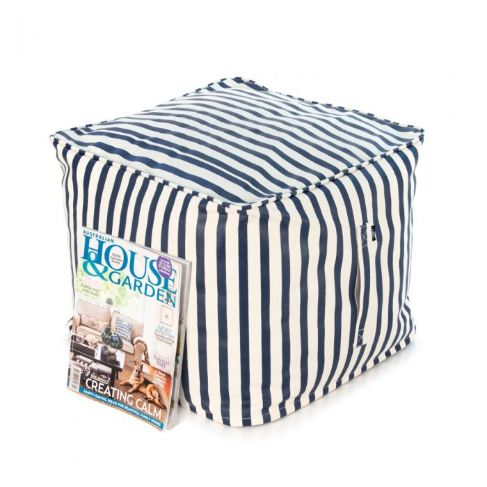 A magazine rests against a blue and white nautcial striped ottoman