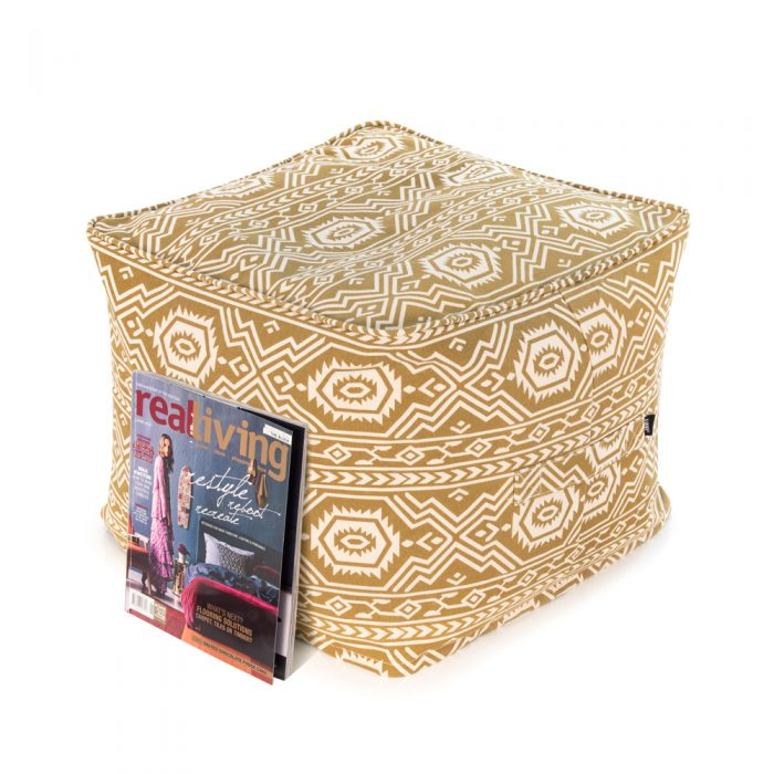 A magazine rests against a mustard yellow tan ottoman with aztec tribal geometric print