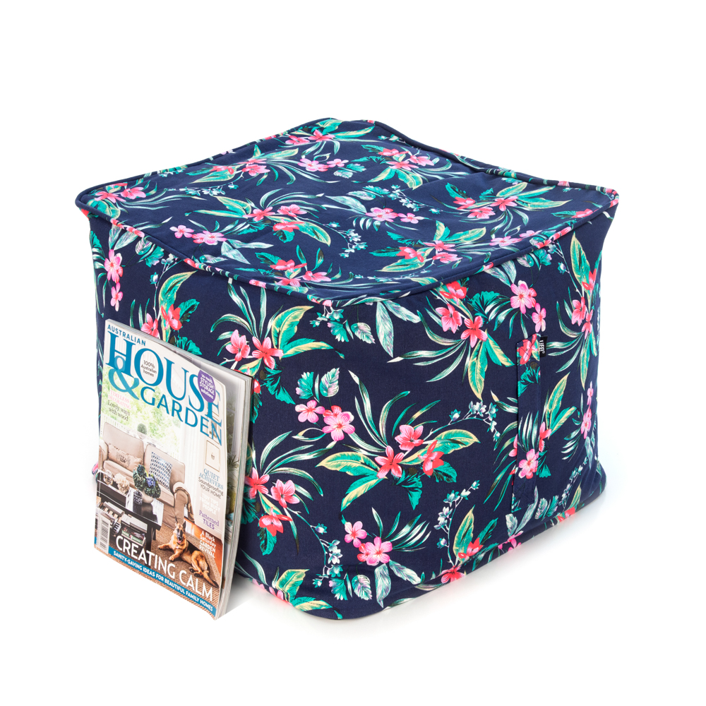 A house and garden magazine rests against a pink and green tropical print on a navy base