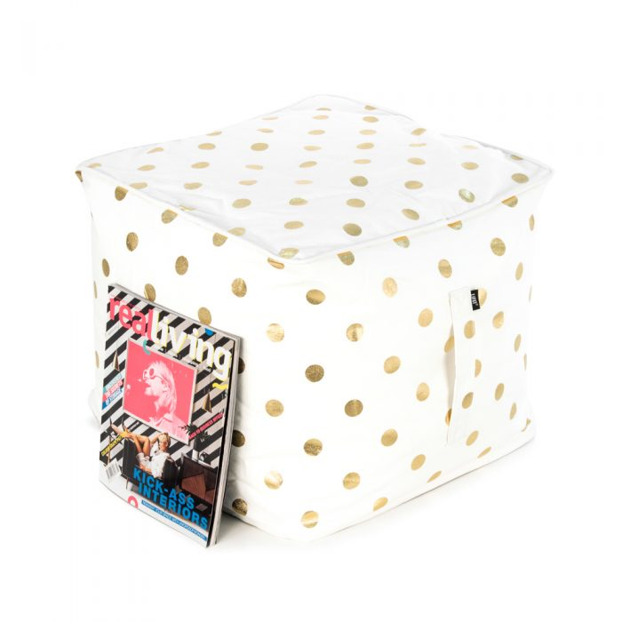 A magazine rests against a white ottoman with a large metallic gold dot print