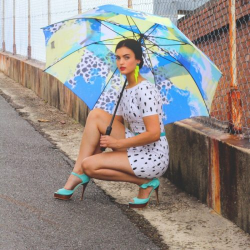 Woman is crouched roadside holding a large, brightly colored rain golf umbrella with a blue, yellow and black spotted pattern