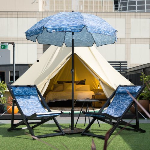 A blue wave print Wellen sun umbrella sits in front of a glamping tent with two matching deck chairs