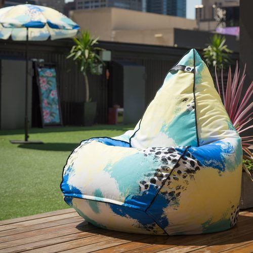Tear drop shaped bean bag in bold abstract hand drawn designer tier fabric in green, blue, yellow and white with black splotches. Bean back is on a deck with a matching umbrella in the background