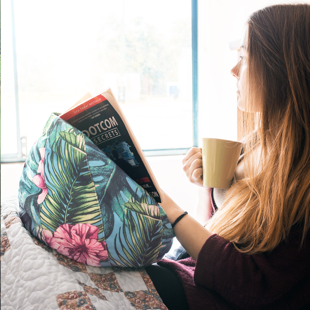 Women drinks coffee and reads a book resting on the belvedere print icrib bean caddy, tablet holder book rest, ipad cushion