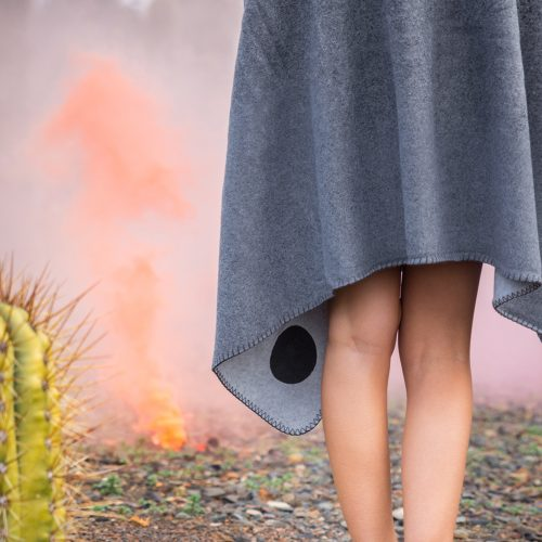 Grey fleece blanket draped around a women showing the stitching detail and a cactus and orange smoke in the background