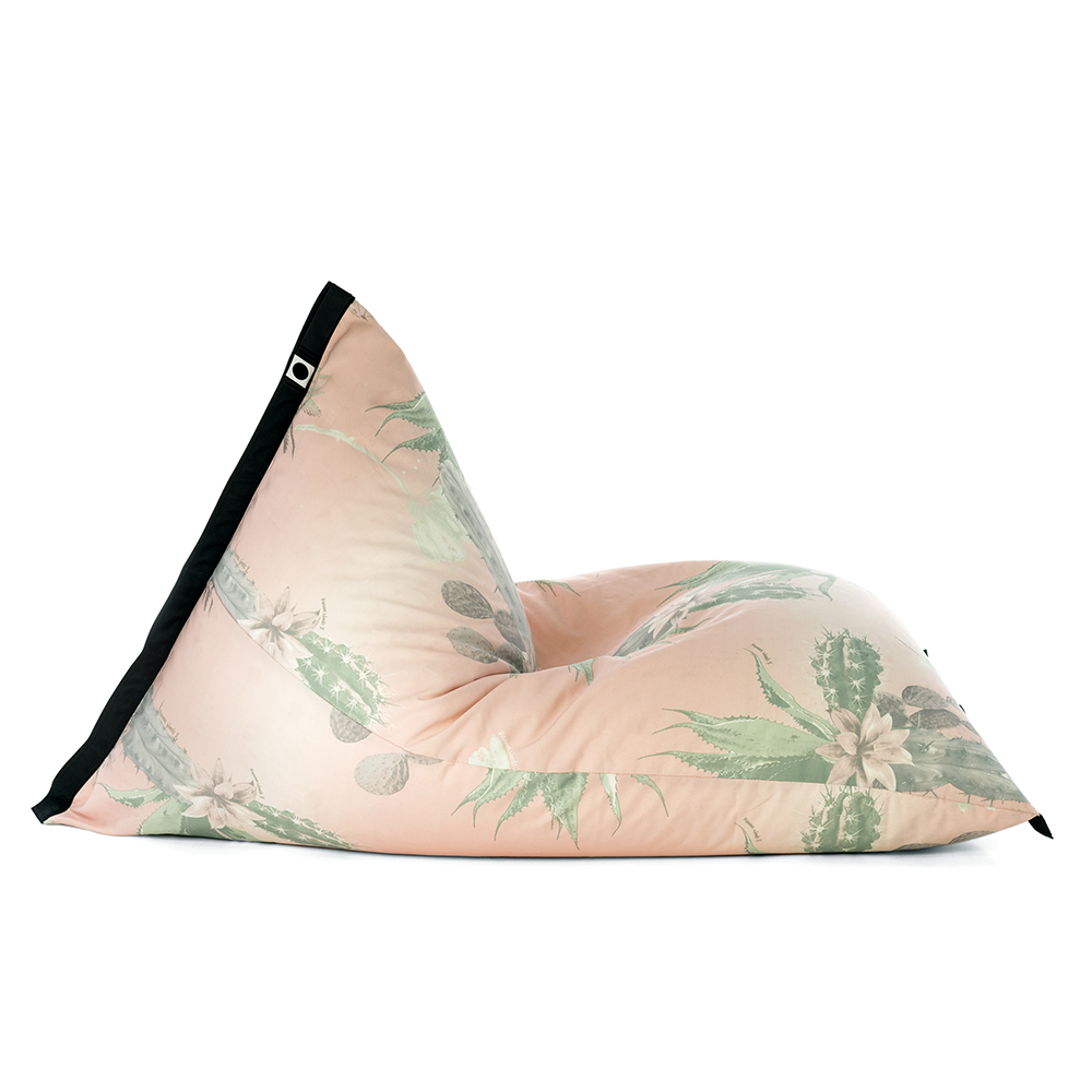 Side view of lifestyle tetrahedral shaped bean bag in pink and green cactus print Kakteen material with black contrast trim
