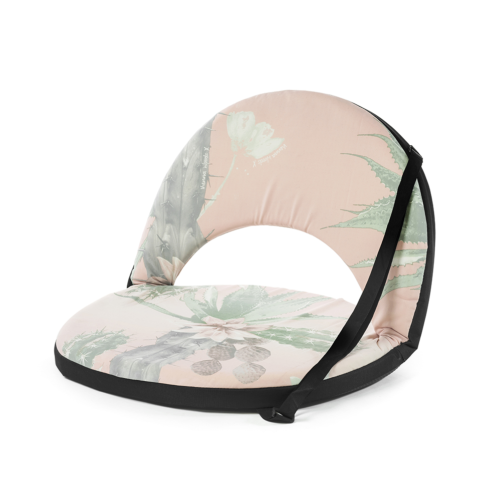 Oblique view of the pink and green kakteen cactus print portable cushion recliner low beach chair seat with black trim and carry strap