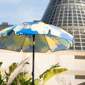 The bright contemporary designer print Tier UPF50+ sun beach umbrella in front of the melbourne shot tower