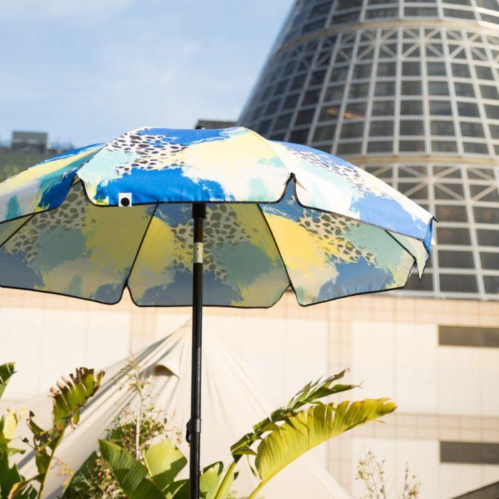 The bright contemporary designer print Tier UPF50+ sun beach umbrella in front of the melbourne shot tower