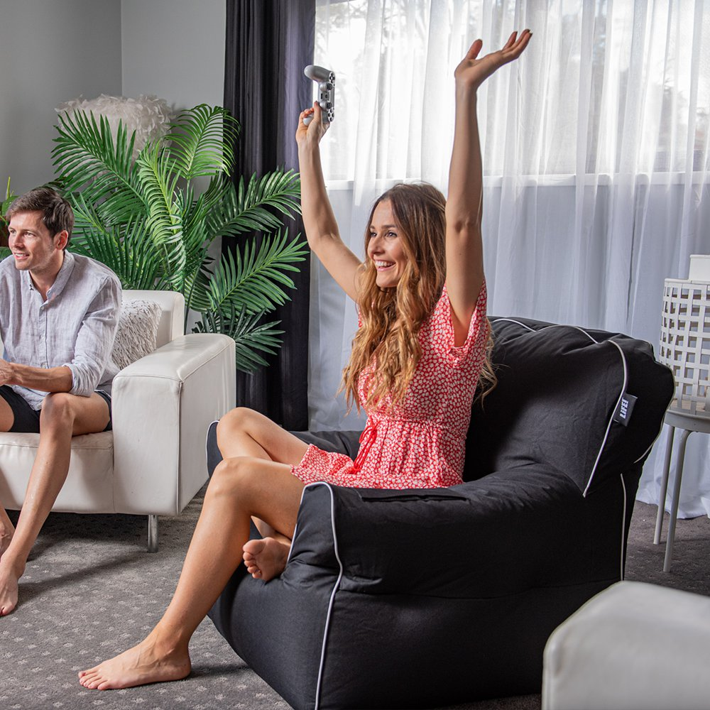 A woman is excited whist gaming seated on a black arm chair chillout bean bag