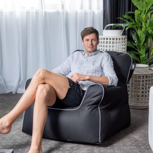 A man sits on a black armchair shaped chillout bean bag