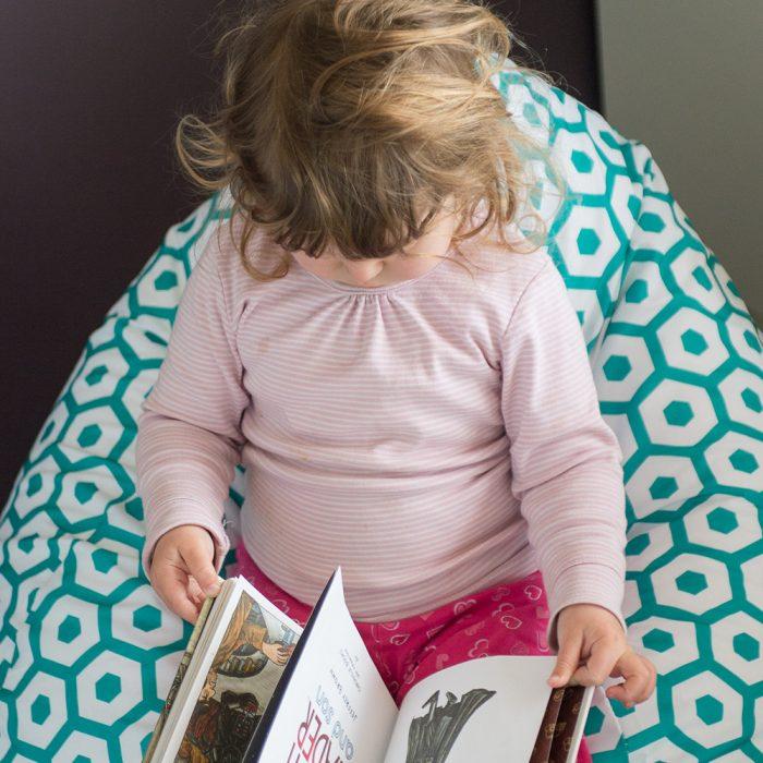 Toddler reads a book on the geo mint teardrop kids bean bag