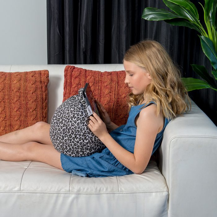 A teen sits on a couch reading from her ipad or tablet that rests in her lap on a grey animal print iCrib bean bag.