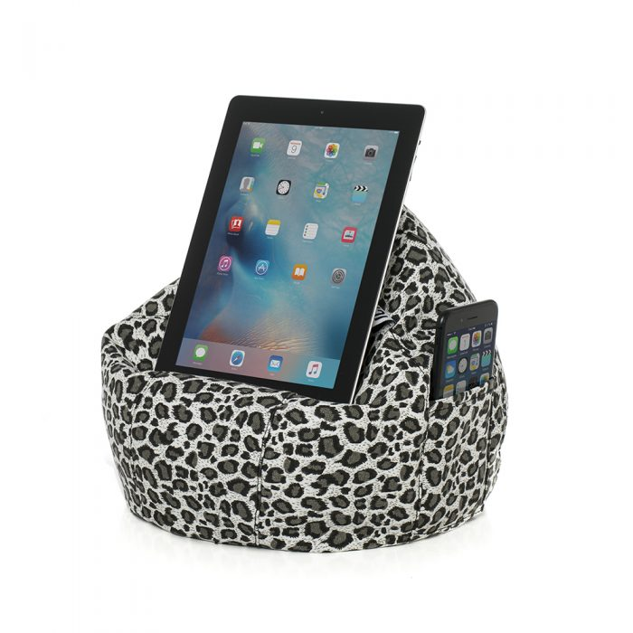 Tan animal print iCrib for resting your iPad, tablet or mobile device on. A phone is visible in the pocket of the faded leopard print iCrib