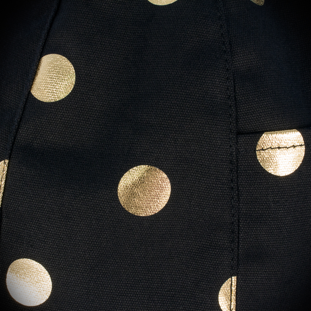 Close up of the black fabric texture with the metallic gold coin print