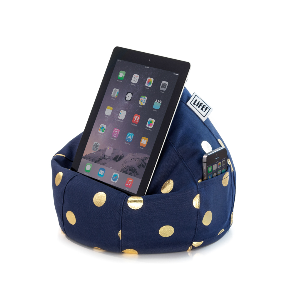 A dark blue iCrib tablet holder iPad rest with metallic gold dot coin print. A mobile phone sits in the storage pocket