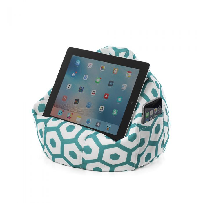 A tablet sits on a green geo mint iCrib iPad holder book rest tablet stand. A mobile phone sits in the storage pocket