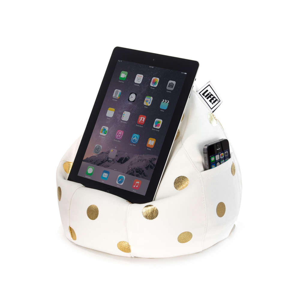 A iPad, tablet or portable device sits on the white iCrib tablet holder, iPad rest, book stand, with metallic gold coin dot print. A mobile phone sits in the pocket.