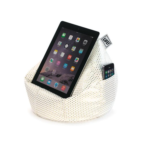 A tablet sits on a white iCrib tablet bean bag book rest with small metallic gold dot print fabric. A mobile phone is in the storage pocket.