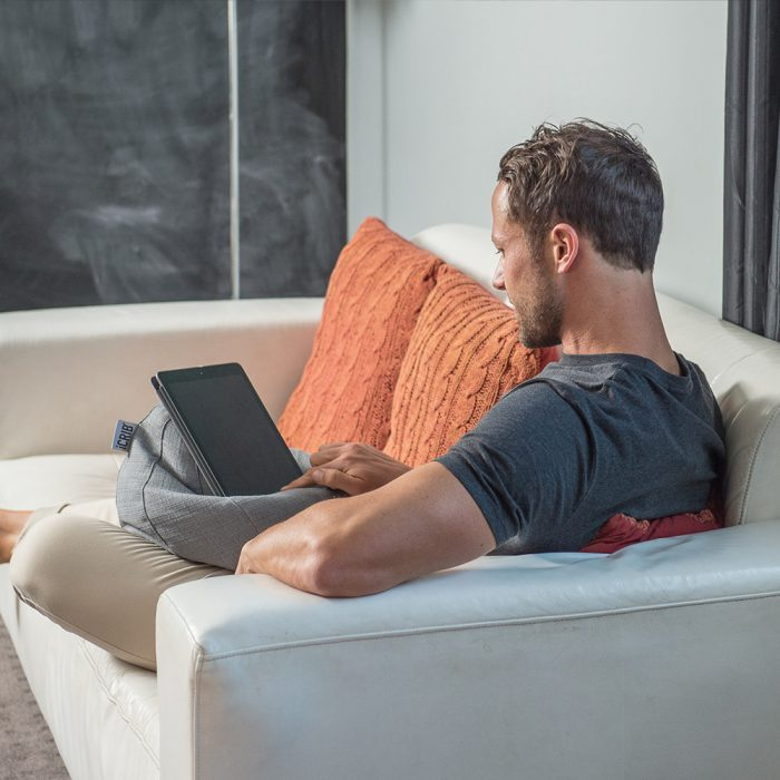 Man sits on a couch using his iPad sitting on a grey linen look iCrib tablet holder bean caddy