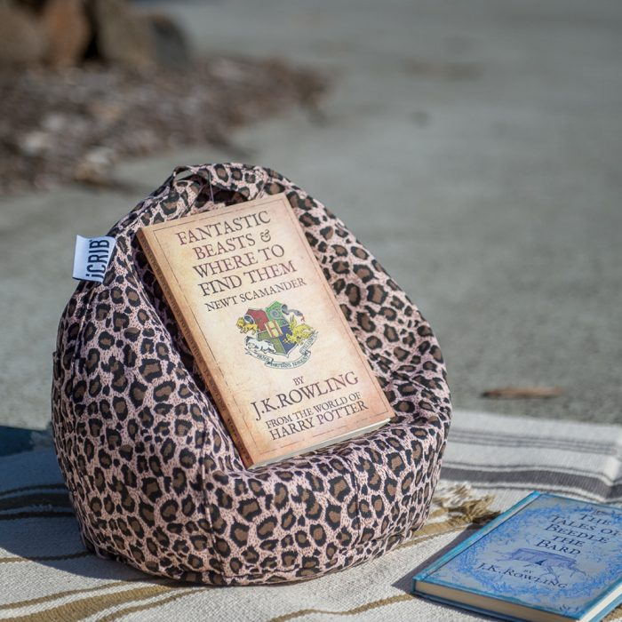 A Harry Potter Fantastic Beasts & Where to Find Them book by J.K. Rowling sits in a brown tan animal print iCrib tablet bean bag book rest, on a cream and brown striped rug outdoors.