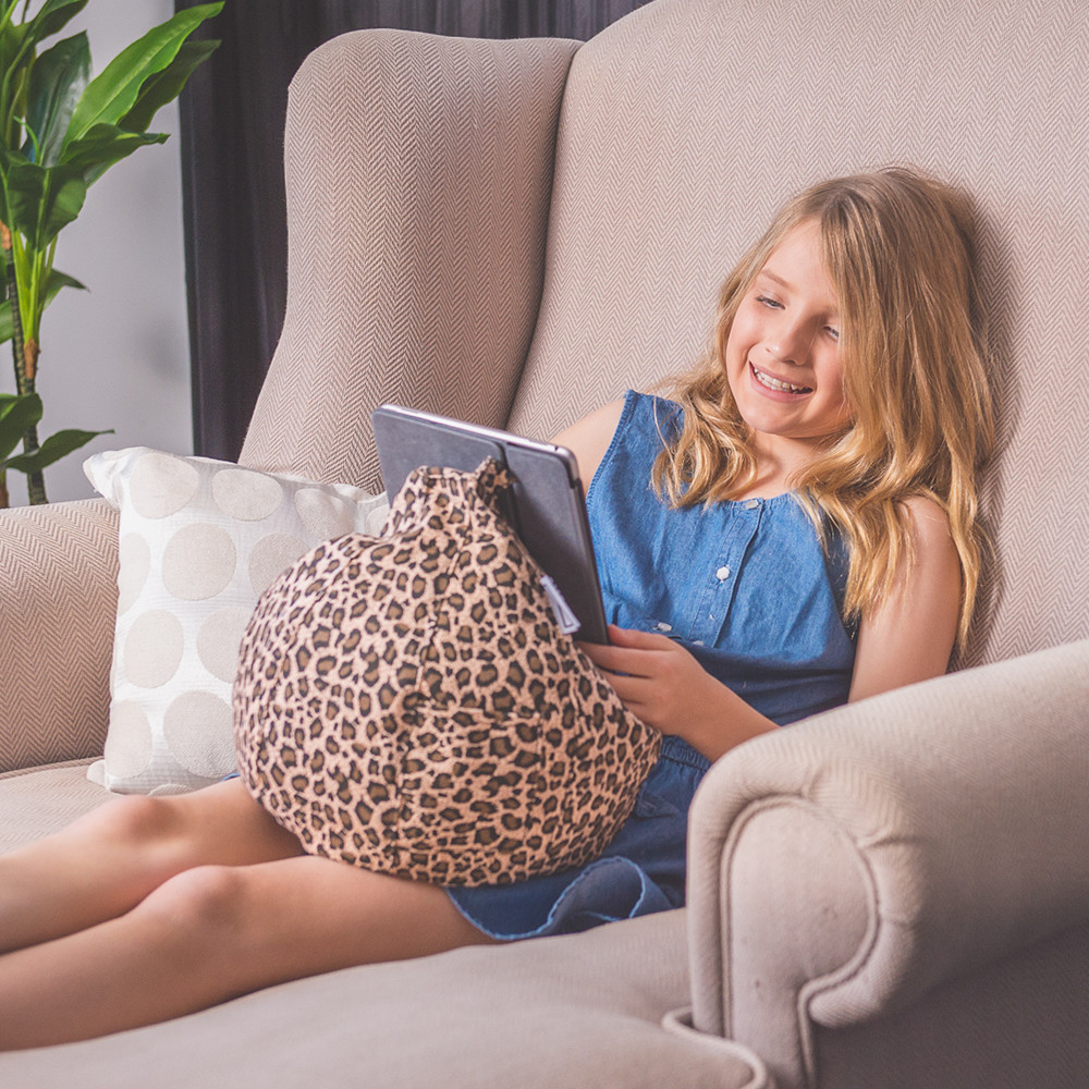 A teen sits on a couch reading from her iPad or tablet that sits in her lap nestled on a brown animal print iCrib bean bag.