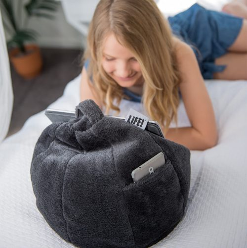 A teen reads from her iPad or tablet hands free with it resting on a slate grey faux fur iCrib bean bag. A smart phone is resting in the storage pocket and the carry handle and LiFE! brand tag are visible.