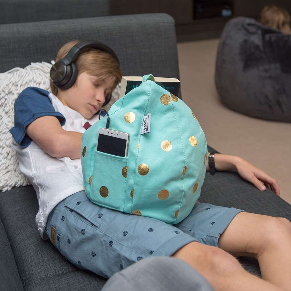Teen sleeps with headphones on and a book nestled in his powder blue cold coin iCrib tablet bean bag. The bean bag caddy also holds an iphone or ipad in the storage pocket.