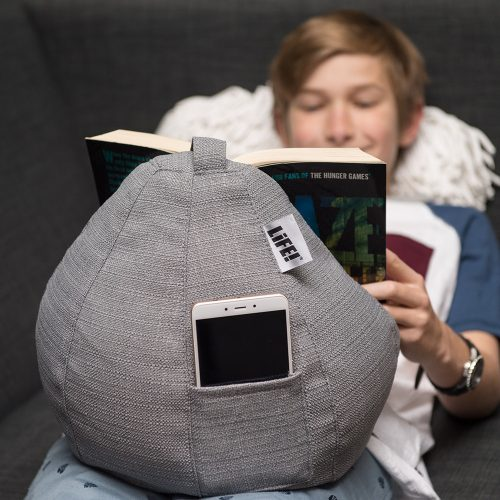 A teen reads a book resting on a grey linen look iCrib tablet holder. His phone sits in the storage pocket