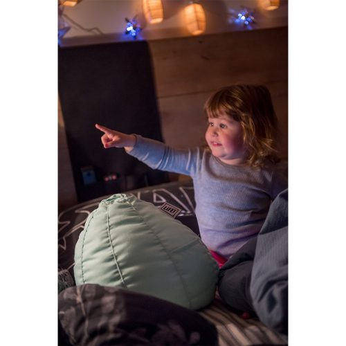 A toddler sits in bed watching an ipad or portable device on a mint green bean filled bean caddy.