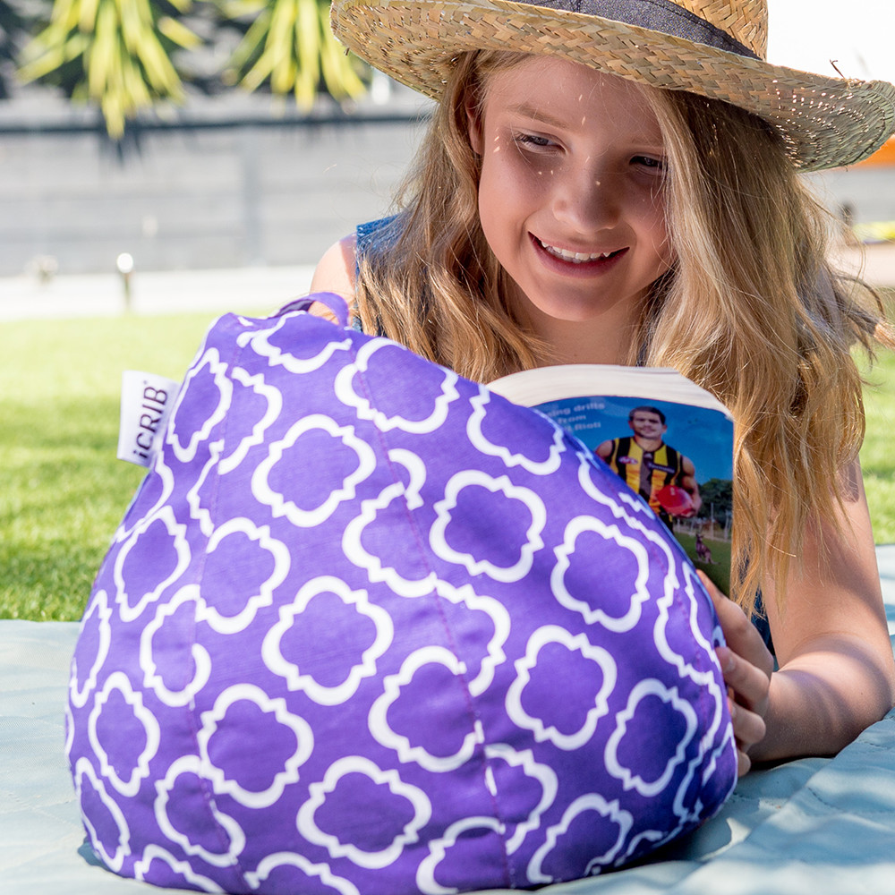 A teen reads a book resting on a purple iCrib bean bag with a white geometric print.