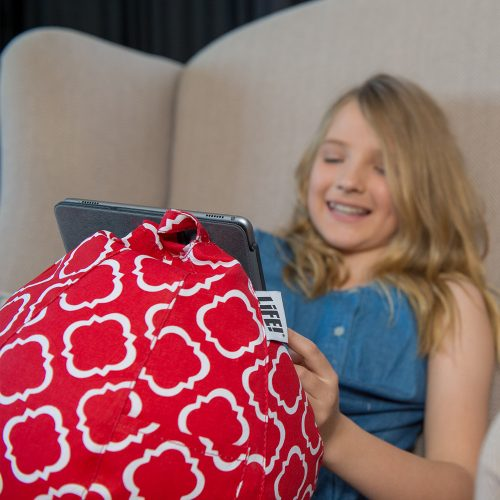 A teen watches her iPad nestled in a red iCrib with white geometric print.